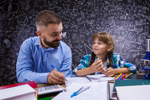 Young hipster school teacher with his pupil in front of big blackboard