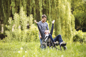 Young hipster son walking with disabled father in wheelchair at park, having fun together. Carer assisting disabled senior man.