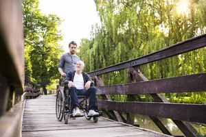 Young hipster son walking with disabled father in wheelchair on wooden bridge at park. Carer assisting disabled senior man.