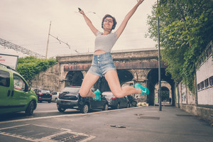young hipster woman listening to music jumping in the city