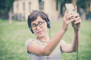 young hipster woman listening to music selfie in the city