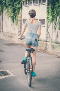 young hipster woman with bike in the city