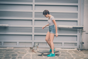 young hipster woman with skate in the city