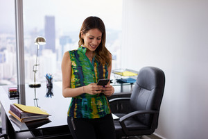 Young hispanic business woman leaning on table in modern office. She holds a mobile phone and is text messaging, smiling happy