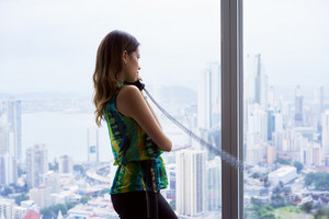 Young hispanic businesswoman in modern office building, with a beautiful sight of the city. She holds a wired telephone with long wire and looks outside window