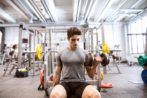 Young hispanic fitness man in gym sitting on bench, working out with weights