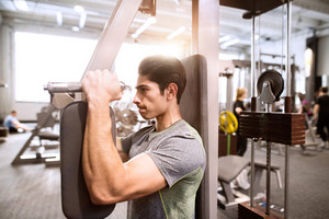 Young hispanic fitness man in gym working on butterfly fitness machine with weights, flexing muscles