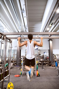 Young hispanic fitness man in gym working out, doing pull-ups on horizontal bar. Rear view.