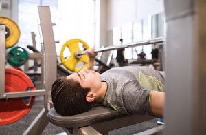 Young hispanic fitness man in gym working out, flexing muscles and making bench press in gym