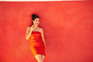 Young hispanic people smoking e-cig, pretty sensual latina woman with electronic cigarette, happy sexy girl smiling and leaning on red wall with copy space. Portrait looking at camera