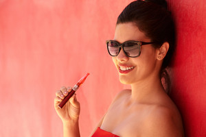 Young hispanic people smoking e-cig, pretty sensual latina woman with electronic cigarette, happy sexy girl with sunglasses smiling and blowing smoke. Portrait looking at camera