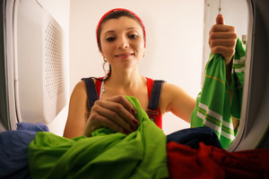 Young hispanic woman at home, doing chores and housekeeping, collecting clothes and dresses from laundry tumble dryer, drying machine