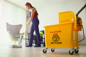 Young hispanic woman at home, doing chores and housekeeping, wiping floor with water in living room