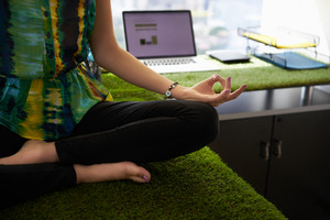 Young hispanic woman in office, sitting on desk covered with grass and plants. She meditates yoga in lotus position. Cropped view of hands and feet