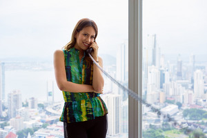 Young Hispanic woman leaning on table in a modern office building, with a beautiful sight of the city in background. She holds a wired telephone with long wire and talks looking away. Copy space