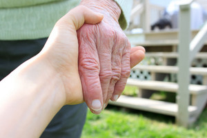 Young holding senior lady's hand in backyard