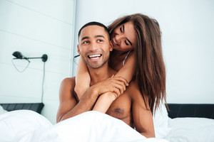Young interracial couple in bed. girl hugging guy from the back. white room