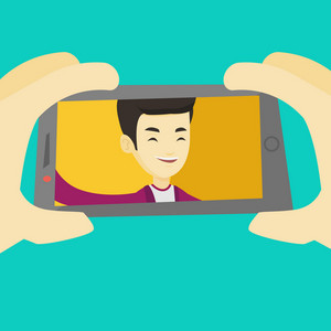 Young joyful asian man making selfie. Smiling man making selfie with cellphone. Man taking selfie. Guy taking selfie using his smartphone. Vector flat design illustration. Square layout.