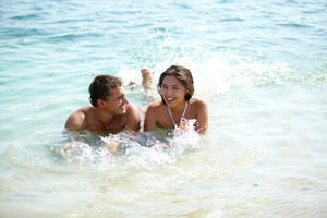 Young joyful couple lying in water and splashing playfully