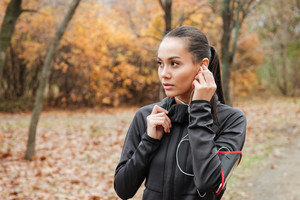 Young lady runner in warm clothes and earphones in autumn park. Look aside.