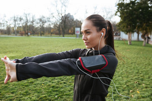 Young lady runner in warm clothes and headphones looking aside in autumn park while make sport exercise