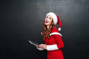 Young laughing woman in red santa claus costume with pc tablet isolated on a black background