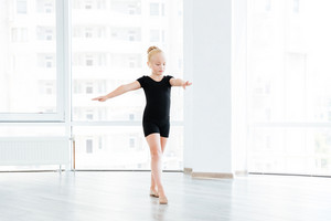 Young little ballet dancing student at a class doing exercises