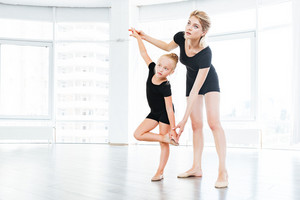 Young little girl ballerina learning dance lesson with female ballet teacher at studio