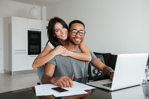 Young loving couple using laptop and analyzing their finances. Looking at the camera.