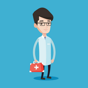 Young male doctor in medical gown holding first aid box. Friendly doctor in uniform standing with first aid kit. Vector flat design illustration isolated on blue background. Square layout.