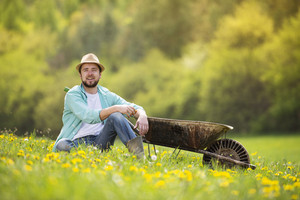 Young male farmer with wheelbarrow is relaxing on the green meadow