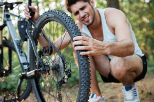 Young male repairing mountain bike in the forest. focus on wheel