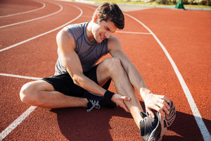 Young male runner suffering from leg cramp on the track at the stadium