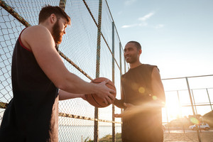 Young male sports man giving basketball to his friend while standing at the playground