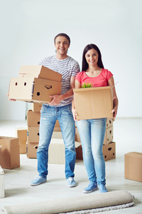 Young man and woman holding packages with domestic things