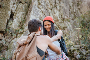 Young man and woman with backpacks walking on rock