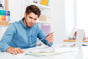 Young man architect holding ruler over diagram on the office desk