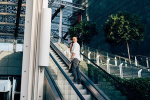 Young man caucasian outdoor in the city talking smart phone on escalator - business call, conversation, communication