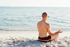 Young man doing yoga on the beach - meditation, relaxing, zen concept