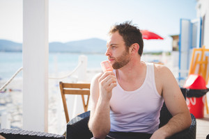 young man eating icecream at the beach bar in summertime