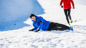 Young man falling while jogging outside in sunny winter mountains