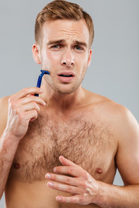 Young man fears to shave isolated on the gray background