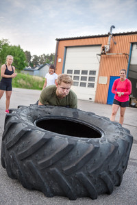 Young man flipping heavy tires outdoor
