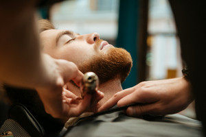Young man getting beard haircut by hairdresser while lies in chair at barbershop.