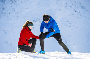 Young man having a knee injury while jogging outside in sunny winter mountains