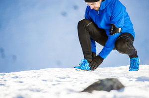 Young man having an uncle injury while jogging outside in sunny winter mountains