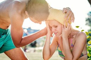 Young man helping woman in bikini with heatstroke, summer heat, sunny day