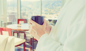Young man in a bathrobe with a cup of coffee in a brightly lit modern interior room