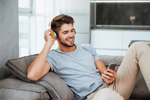 Young man in headphones listening to music while lies on sofa. Looking on phone and chatting.