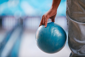 Young man in jeans holding bowling ball